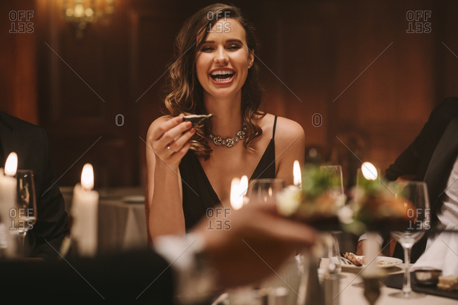 Beautiful woman laughing while having dinner with friends at a party. Pretty female enjoying at a gala dinner party.