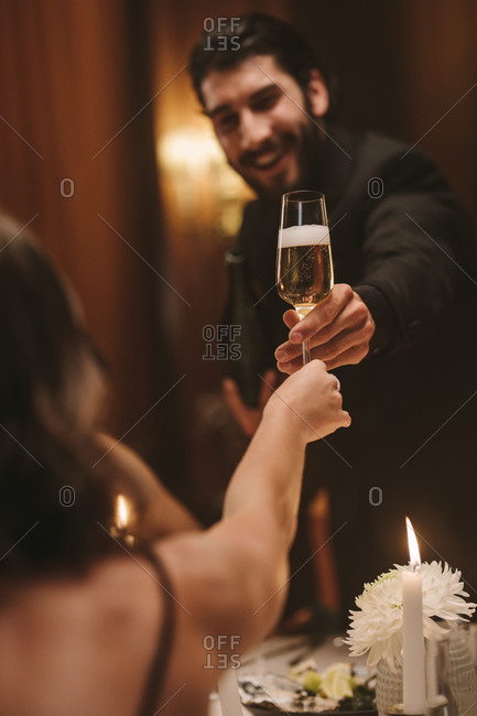 Handsome man giving a champagne glass to a female friend at dinner party. Man passing drinks to guest at dinner party.
