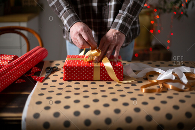 Man's hands packing holiday gifts