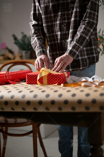 Man's hands packing holiday gifts, polka dots wrapping paper