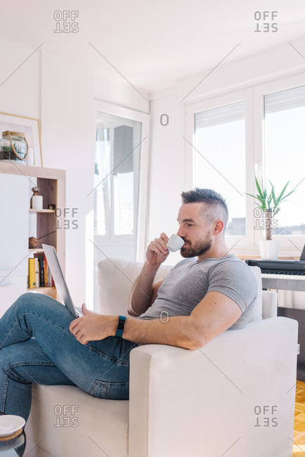 Young man working from home and drinking coffee