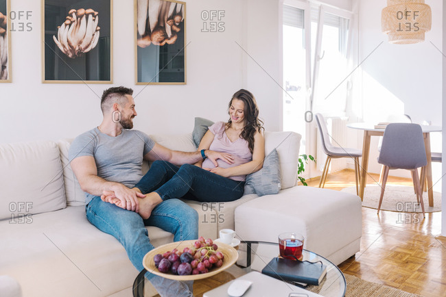 Young couple expecting their first child husband touching wife's belly