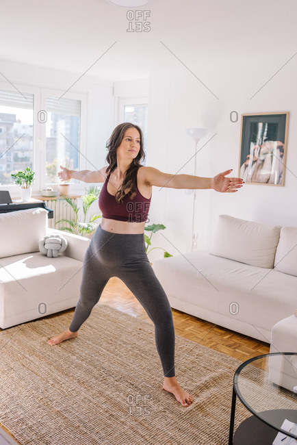 Pregnant woman in sportswear standing and doing yoga poses in her living room