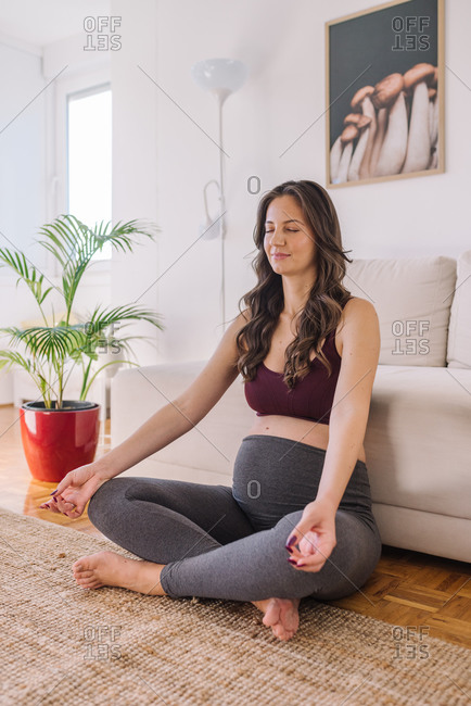 Young pregnant woman meditating in her living room