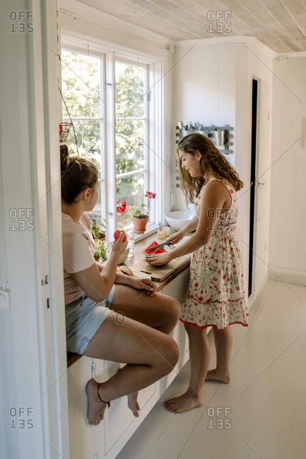 Siblings talking while eating watermelon in domestic kitchen