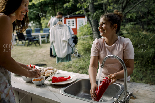 Smiling daughter and mother talking while preparing food in yard during summer