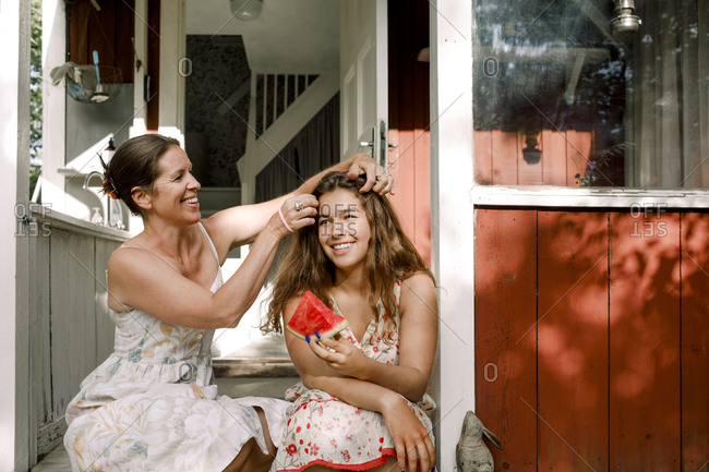 Smiling mother tying daughter's hair while sitting outdoors