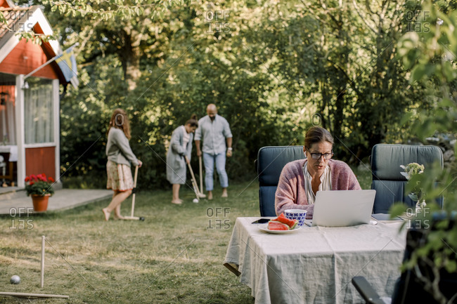 Woman using laptop while family playing in background at yard