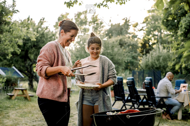 Smiling mother and daughter looking at red chili pepper over barbecue grill in yard