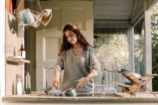 Teenage girl washing utensil in sink outside house
