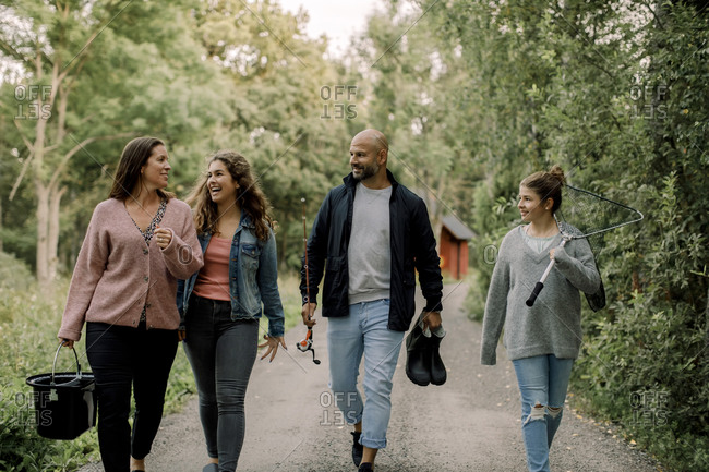 Smiling daughters with father and mother on footpath during vacations