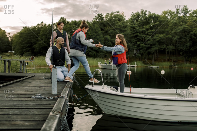 Parents looking at daughter holding sister's hand while standing in boat over lake