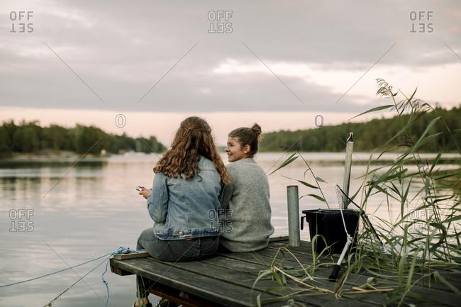 Smiling girl talking to sibling while sitting on pier during sunset