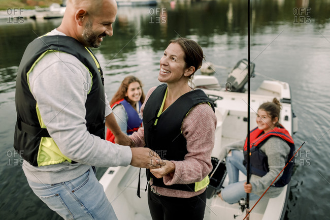 Daughters looking at parents holding hands while sitting in boat