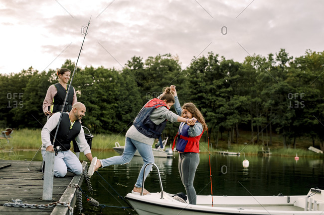 Parents looking at smiling daughter holding sister's hand while standing in boat over lake