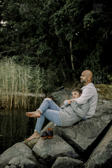 Father and daughter looking away while sitting on rock by lake