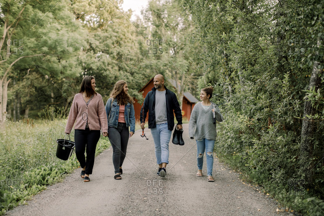 Smiling daughters with father and mother walking on footpath during vacations