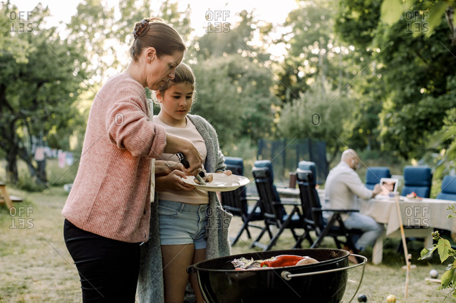 Side view of mother and daughter preparing food over barbecue grill in yard