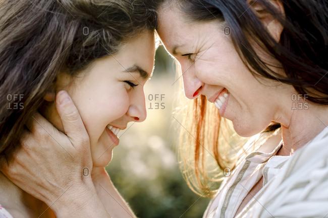 Smiling mother embracing daughter in yard