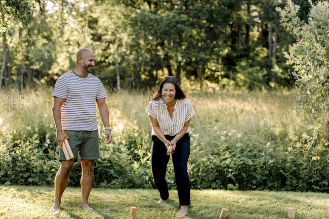 Cheerful woman with male partner playing molkky in yard