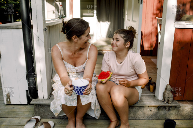 Cheerful mother talking to daughter eating slice of watermelon outdoors