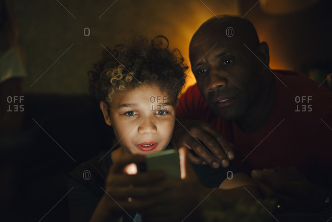 Boy using smart phone by father in living room at night