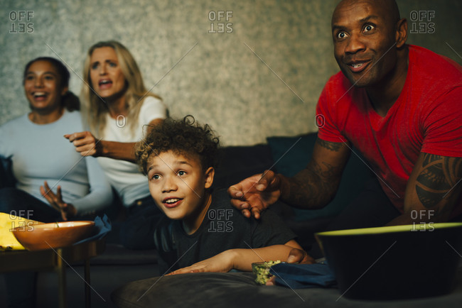 Excited sports fans watching TV together at night