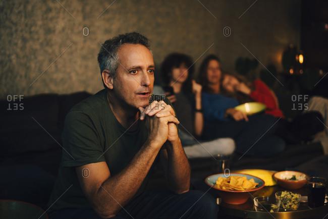 Hopeful man praying while watching sports in living room at night