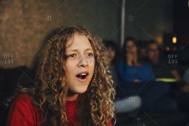 Smiling girl with family watching sports in living room at night