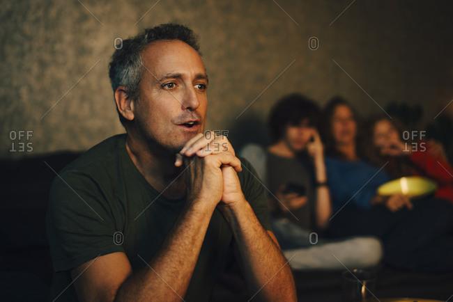 Hopeful man praying while watching sports at night