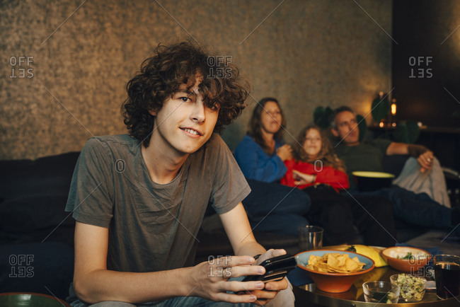 Portrait of teenage boy using smart phone while family watching sports in background at night