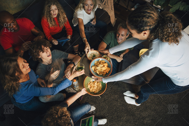 High angle view of smiling teenager giving nacho chips to family during sporting event