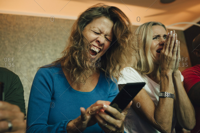 Happy woman cheering by friends while watching sports on smart phone in living room
