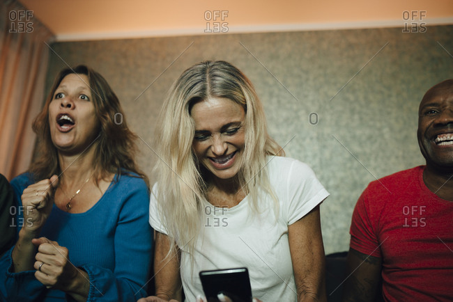 Smiling woman using smart phone by friends during sporting event