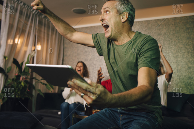 Excited man cheering while using digital tablet during sporting event