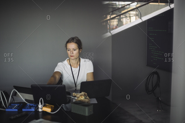 Female IT professional typing on laptop in office