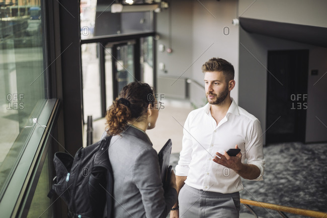 Business professionals discussing in corridor at workplace