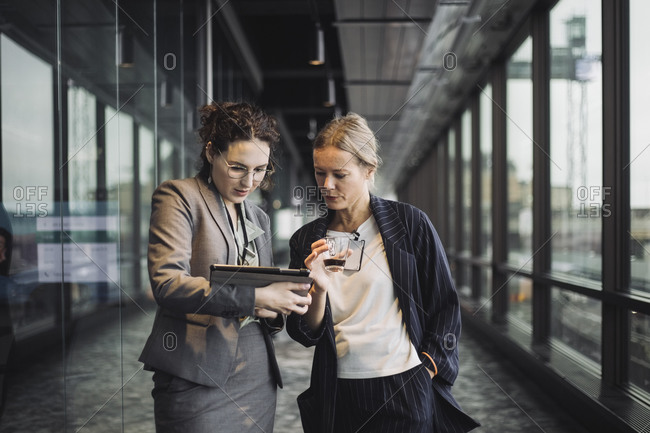 Female business professionals discussing in corridor at workplace