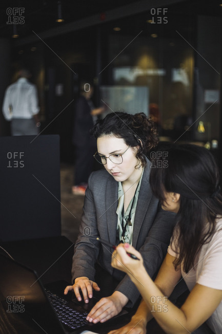 Side view of female professionals working on laptop in office