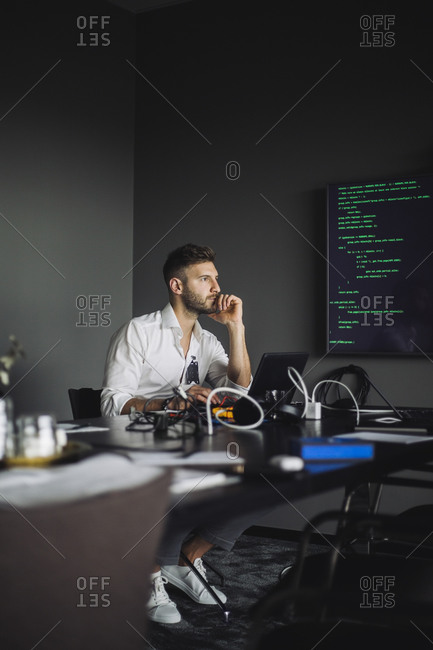 IT professional with hand on chin contemplating in creative office