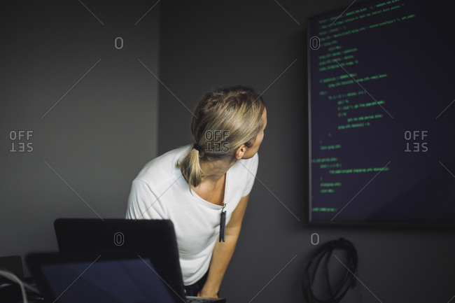 Female computer professional looking at projection screen in creative office