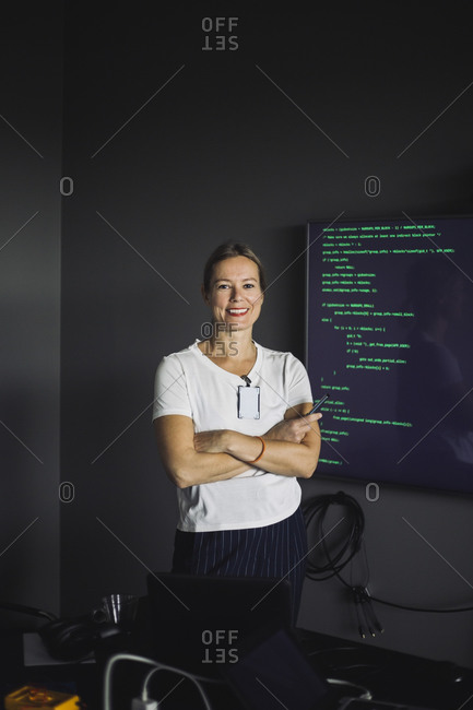 Portrait of smiling IT professional working on projection screen in creative office