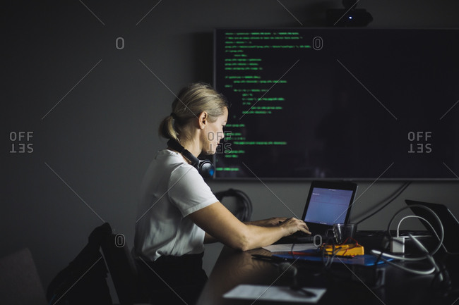 Female IT professional typing on laptop in creative office