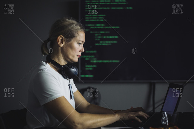 Side view of IT professional working on laptop in office
