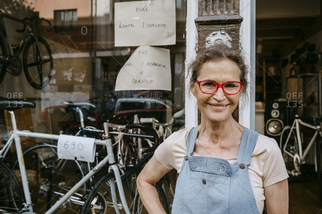 Portrait of confident female owner wearing funky eyeglasses while standing against bicycle shop