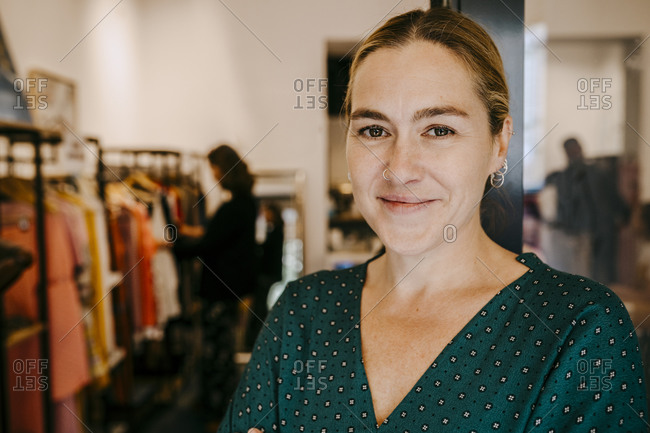 Portrait of smiling female owner at doorway of store
