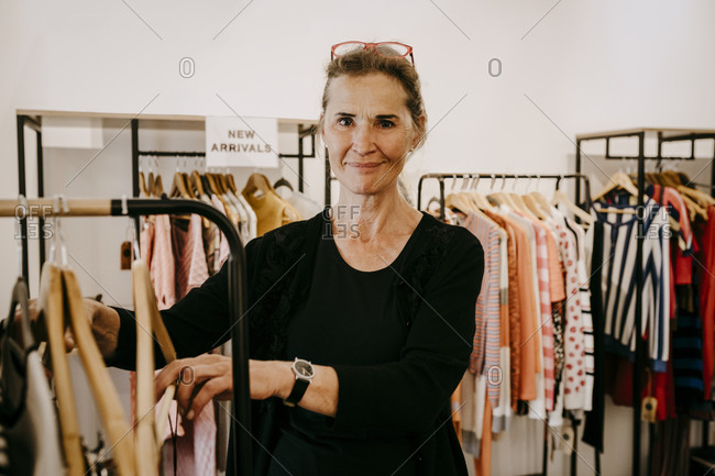 Portrait of smiling senior owner arranging clothes in store