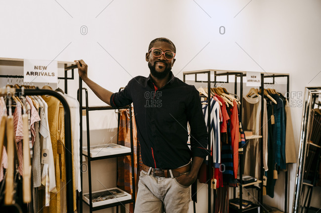 Portrait of smiling owner standing in clothing store