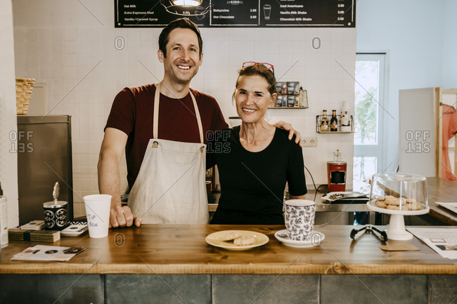 Portrait of smiling senior owner and male employee standing in coffee shop