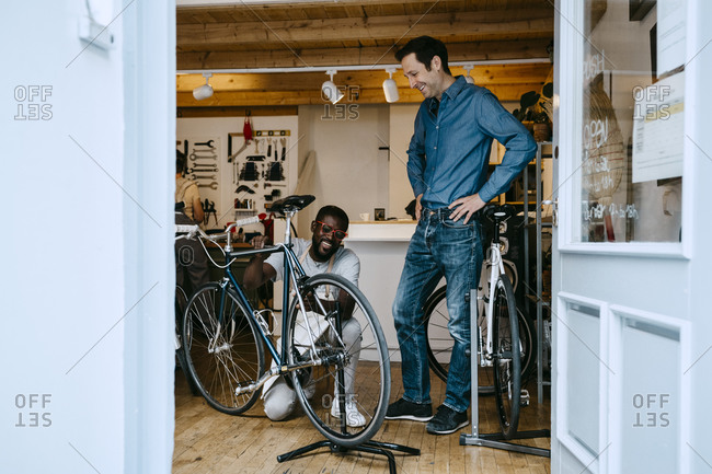 Smiling owner repairing bicycle in workshop by colleague seen through glass window